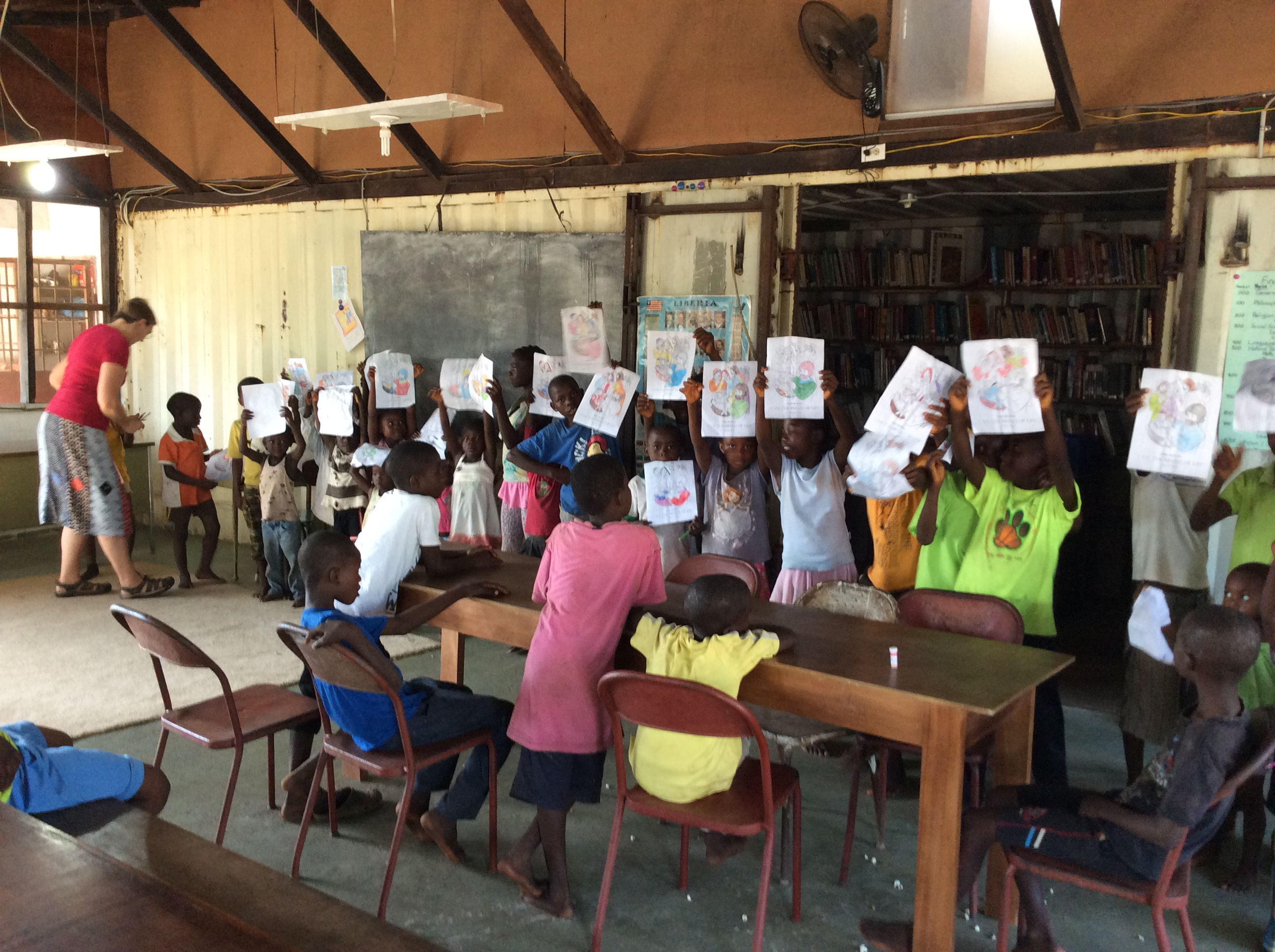 Students hold up their colouring work, (about 20) standing in a line. some are sitting and watching.